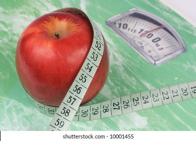 Apple and tape measure on a scale