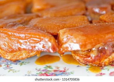 Apple tarte tatin close up with drop of caramel dripping.