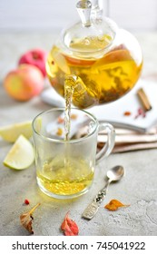 Apple tea with slices is poured from a glass teapot into a glass, still life with apples, light background