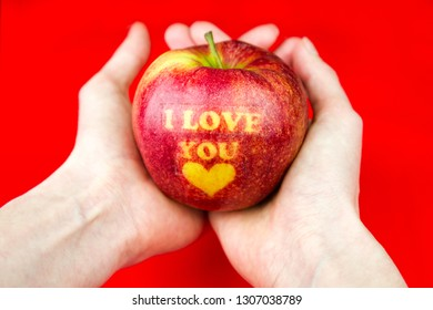 Apple with text I LOVE YOU in hands on red background. Valentine's Day concept.