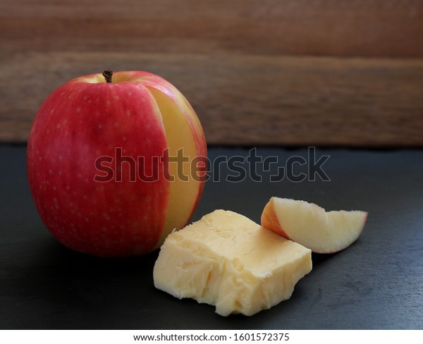 Apple with a thin slice removed. Resting against crumbly cheddar cheese. Typical sweet and savoury snack. Subdued lighting on the apple makes cheese and apple slice  combination the focal point.