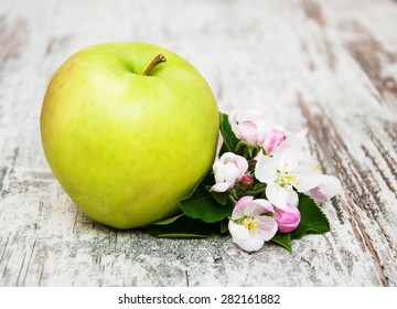 apple and apple tree blossoms on a old wooden table
