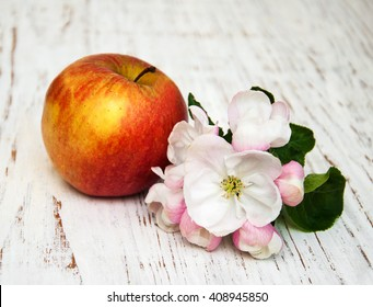 apple and apple tree blossoms on a wooden background