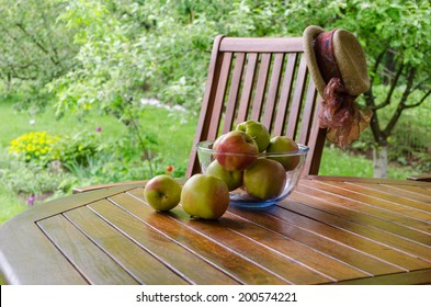 Apple tree fruits in glass dish on bower table in garden.