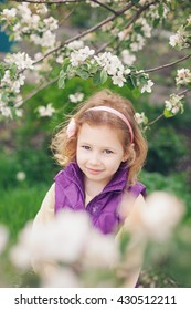 Apple trees in bloom. Beautiful little girl enjoying the aroma of apple blossom