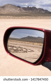 Apple Valley, CA/ USA- June 1 2019:  In a red car's rear view mirror, there is a labyrinth in the high desert and in front of the mirror is an arid landscape with mountains and sand in the distance.
