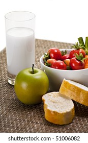 Apple with Vegetables Bread and Glass of Milk on Placemat