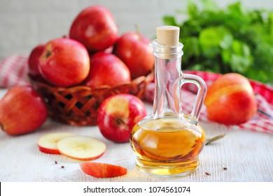 Apple vinegar. Bottle of apple vinegar on wooden background. Healthy food.