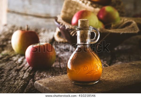 Apple vinegar. Bottle of apple organic vinegar on wooden background. Healthy organic food.