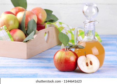Apple vinegar with fresh ripe apples on a blue wooden background