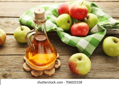 Apple vinegar in glass bottle on grey wooden table