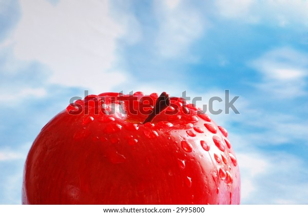Apple with  water drops against the blue sky