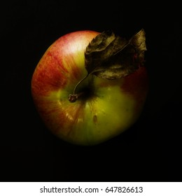 Apple with withered leaf on black background. Top view.