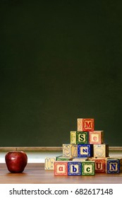 Apple and wooden blocks in front of chalkboard