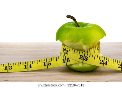 Apple wrapped with measuring tape on wooden surface. Healthy diet concept. Selective focus.