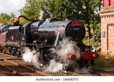 APPLEBY, ENGLAND - AUGUST 18:  Preserved Stanier Class 8F steam locomotive number 48151 takes on water in Appleby, England on August 18, 2013, on the Settle to Carlisle railway.