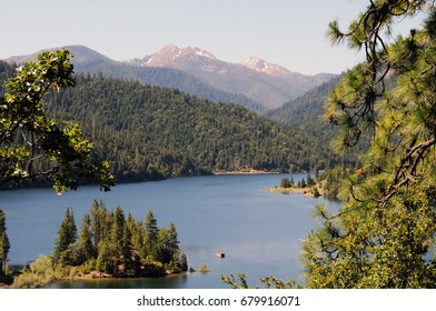 Applegate Lake, Oregon, surrounded by green, lush forests and craggy mountains touched by snow.