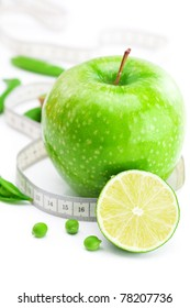 apple,lime,peas and measure tape isolated on white