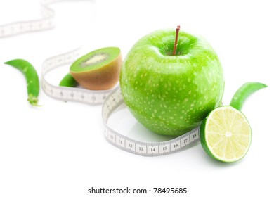 apple,lime,peas,kiwi and measure tape isolated on white