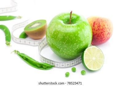 apple,lime,peas,kiwi ,peach and measure tape isolated on white