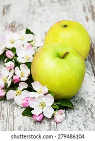 apples  and apple tree blossoms on a old wooden table
