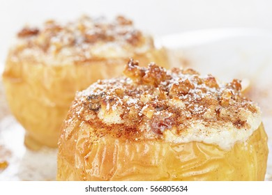Apples baked with cottage cheese and raisins, decorated with nuts, cinnamon and powdered sugar