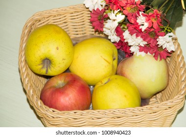 Apples in the basket. Bouquet of flowers. Harvest.
