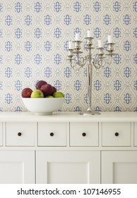 Apples in bowl and candlestick in front of patterned wall