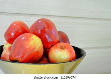 apples in a bowl on wood background