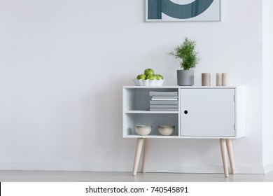 Apples in bowl, plant in grey pot and candles on white modern cupboard against white wall
