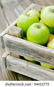 Apples in the box. Green apples on a wooden table.