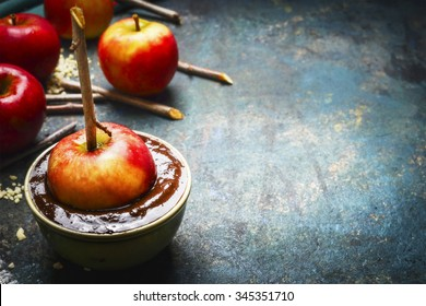 apples in chocolate coating with sticks on rustic background