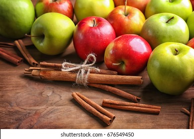 Apples with cinnamon sticks on wooden background