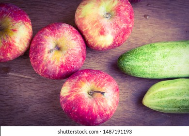 Apples and cucumbers placed on a wooden table