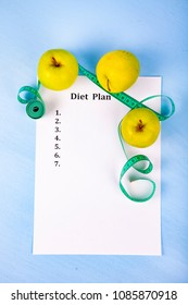 Apples, diet plan,dumbbells and measuring tape on a wooden background. Concept of diet and healthy lifestyle.