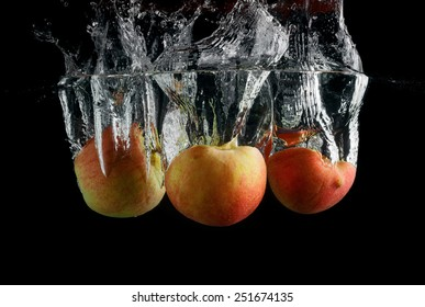 Apples are falling into the water with a splash. Photo on black background.