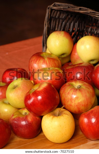 Apples falling out of a woven basket onto a table