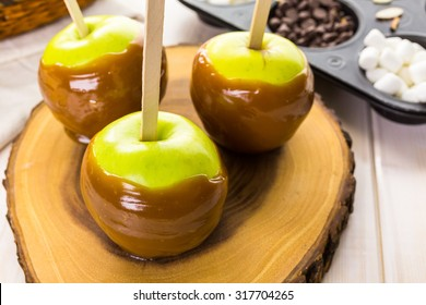 Apples freshly dipped in caramel on cutting board.