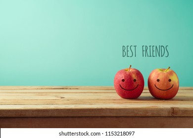 Apples with funny faces on wooden table. Friendship day celebration background