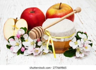 Apples with honey and apple tree flowers on a wooden background