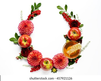 Apples and honey with honeycomb and dahlias with copy space form a floral decoration for Rosh Hashanah the Jewish New Year.