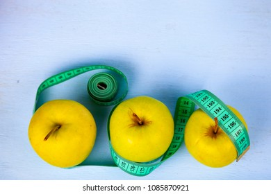 Apples and measuring tape  on a blue wooden background, top view.  Concept of diet and healthy lifestyle.