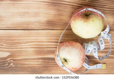 Apples and measuring tape on wooden background
