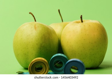 Apples near measuring tape rolls on green background, close up. Diet and sport regime concept. Pattern made of apple fruits near blue and yellow tape measures. Sports and healthy lifestyle symbols