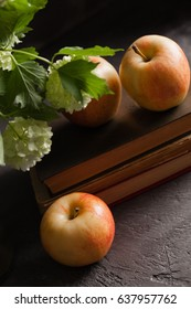 Apples on books on a dark background