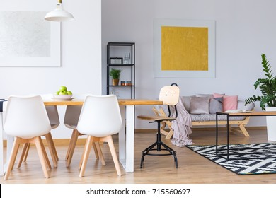 Apples on dining table with white chairs in open space with gold and silver painting