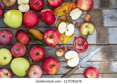 Apples on the wooden gray table with knife and colorful leaves nearby, fruit background, autumn concept
