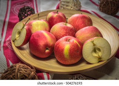 Apples on a wooden plate decorated with rattan balls