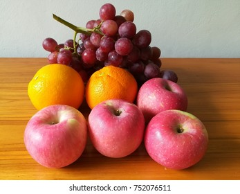Apples oranges and grapes on wooden table against white wall background.