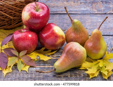 Apples, pears, autumn leaves, still life on a wooden surface